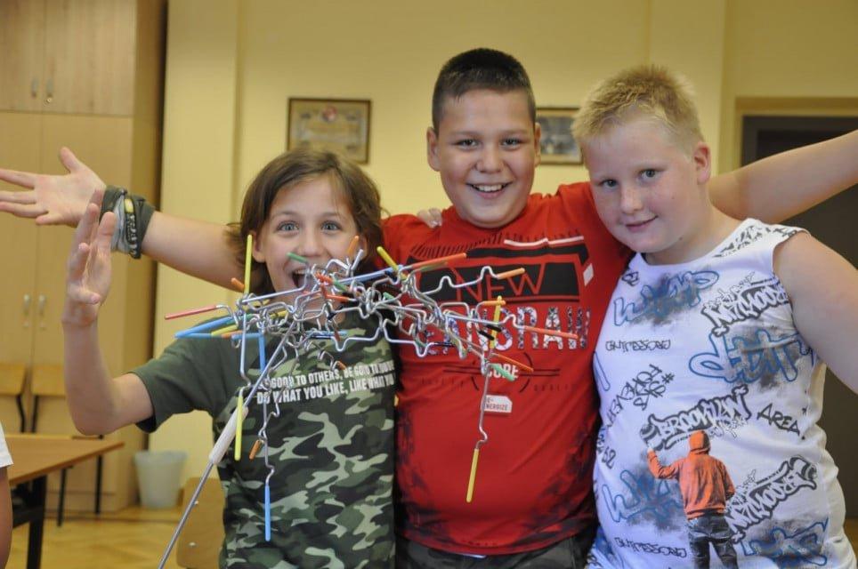 trzech uczestników półkolonii pozuje do zdjęcia, obok konstrukcja zbudowana z metalowych elementów
