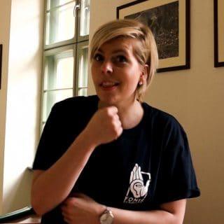 """Młoda kobieta pokazuje w języku migowym znak słowa """"senior"""""""