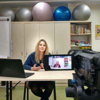 W pomieszczeniu szkoły rodzenia przy biurku siedzi kobieta, którą widać w obiektywie kamery