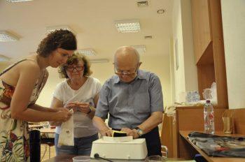 Seniorzy pod opieką pani Kingi wykonują kolorowe witraże