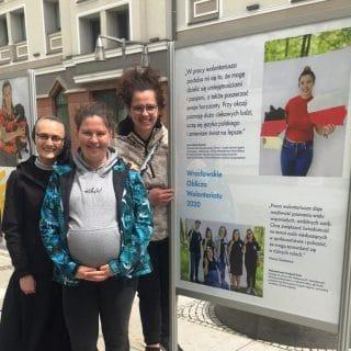 Trzy wolontariuszki przy tablicy wystawowej prezentującej Fundację FONIS