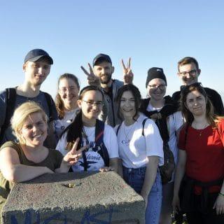 Zdjęcie grupowe 9 wolontariuszy na wieży na szczycie Ślęży
