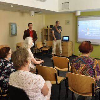 grupa seniorów w sali wykładowej uczestniczy w zajęciach, przed nimi dwóch prelegentów przy tablicy, na której wyświetlana jest prezentacja
