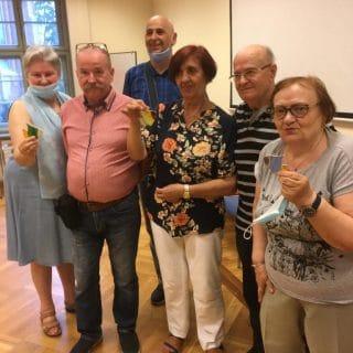 Grupa seniorów w sali pokazuje własnoręcznie wykonane witraże w kształcie ryby