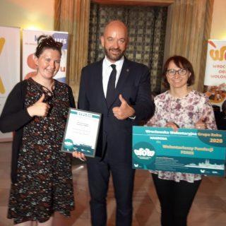 Dwie wolontariuszki Fundacji FONIS trzymają nagrody. Między nimi Prezydent Wrocławia - Jacek Sutryk