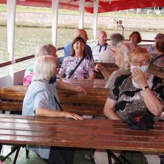 Grupa seniorów siedzi przy stolikach na pokładzie statku