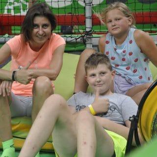 Dwójka dzieci z panią wychowawczynią siedzi w parku trampolin