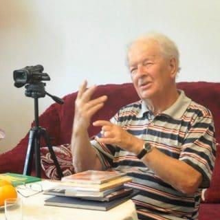 Pan Antoni Morawski udziela wywiadu, siedząc przy stole na którym leżą książki, obok ustawiona kamera