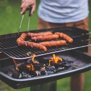 Osoba szczypcami przekłada kiełbasę na grillu