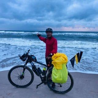 Mężczyzna stoi na brzegu morza z rowerem i ręką wskazuje morze