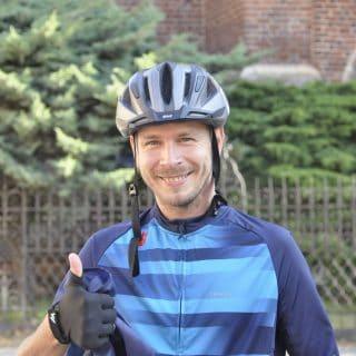 Zdjęcie portretowe Arkadiusza w stroju kolarskim i z kaskiem na głowie, który pokazuje kciuk podniesiony do góry