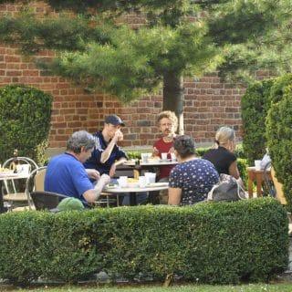 Kilka osób siedzi przy stolikach w ogrodzie