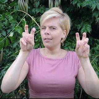 Blondynka na tle zielonych krzewów zaprasza w języku migowym na XII Niepowtarzalne Spotkanie