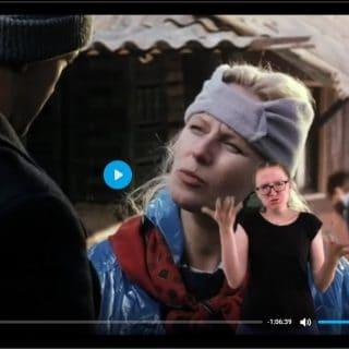 Kadr z filmu zwolnieni z życia. Widoczna twarz Krystyny Jandy, a obok tłumaczka języka migowego