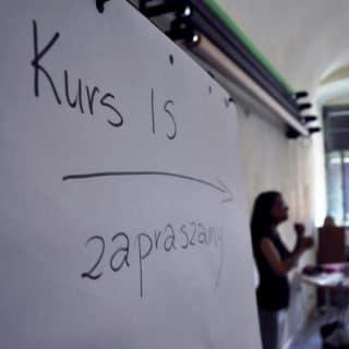 Tablica z napisem kurs IS zapraszamy, obok rozmazana postać prowadzącej zajęcia