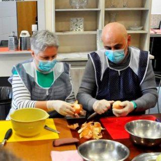 Dwoje seniorów w fartuszkach i maseczkach, siedzą przy stole, na którym stoją miski i obierają cebulę