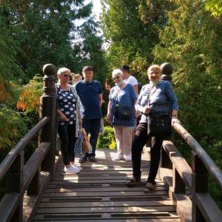 Kilkoro seniorów na mostku w Ogrodzie Japońskim
