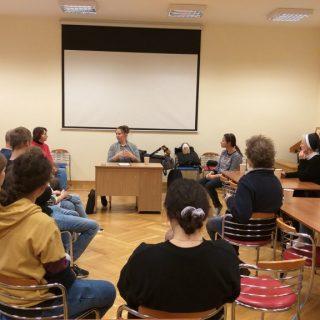 Grupa wolontariuszy siedzi w okręgu w sali, na ścianie ekran do prezentacji