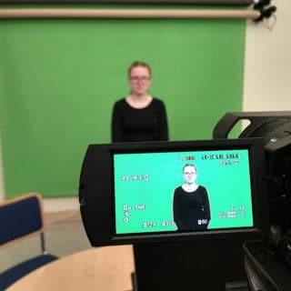 Kobieta ubrana na czarno na zielonym tle zwisającym ze ściany, przed nią kamera. Kobieta widoczna jest też na wyświetlaczu kamery