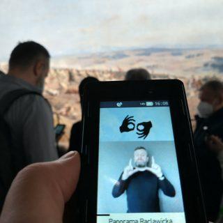 Ekran z przewodnikiem w języku migowym, w tle osoby oglądające Panoramę Racławicką